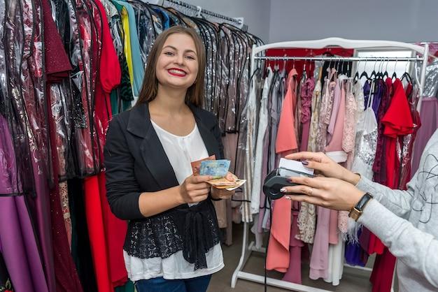 Mulher em loja de roupas com notas de euro Foto Premium