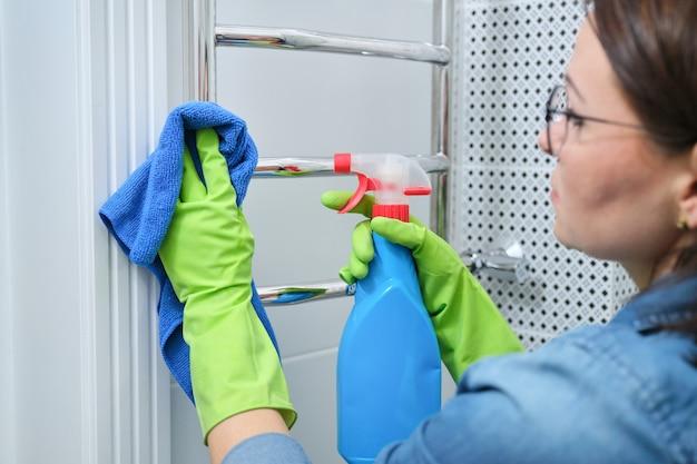 Mulher em luvas com detergente para limpar polimento cromo aquecido toalheiro
