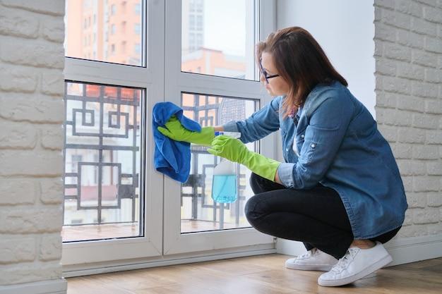 Mulher em luvas com pano de microfibra pulverizado com detergente janela de vidro limpo