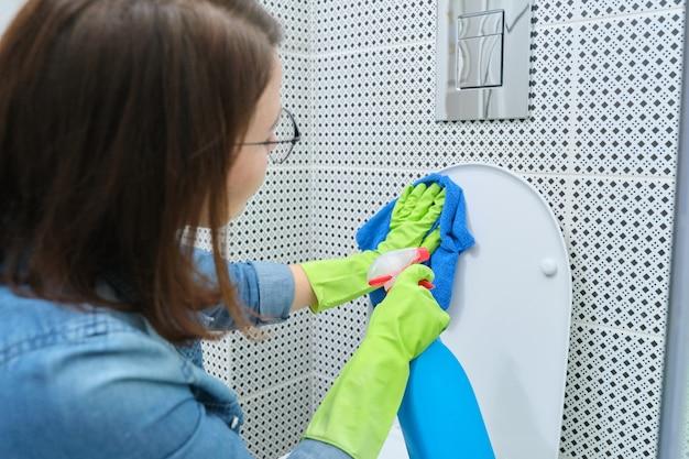 Mulher em luvas com pano e detergente para limpar o vaso sanitário, limpeza doméstica no banheiro
