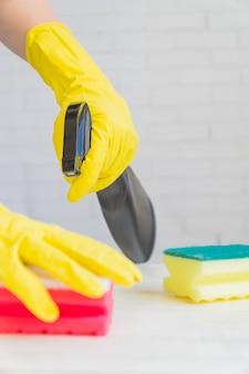 Mulher em luvas de borracha amarelas, segurando a esponja de limpeza. limpar a cozinha branca depois de cozinhar