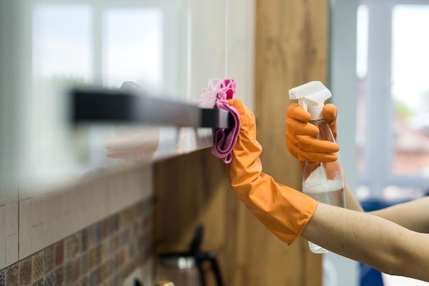 Mulher em luvas de borracha e limpando o balcão da cozinha com uma esponja. tarefas domésticas