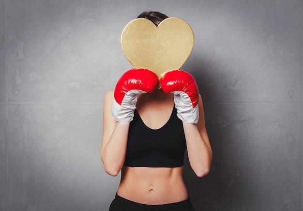 Mulher em luvas de boxe com caixa de presente de forma de coração nas mãos