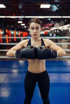 Mulher em luvas de boxe pretas estende as mãos, vista frontal, treinamento de caixa no ringue. boxer feminina na academia, kickboxer feminina no clube desportivo, prática de socos