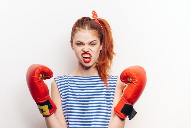 Mulher em luvas de boxe vermelhas e vista frontal da t-shirt listrada. foto de alta qualidade