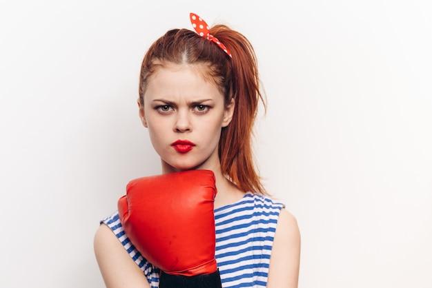 Mulher em luvas de boxe vermelhas em um modelo de emoções de agressão de fundo claro