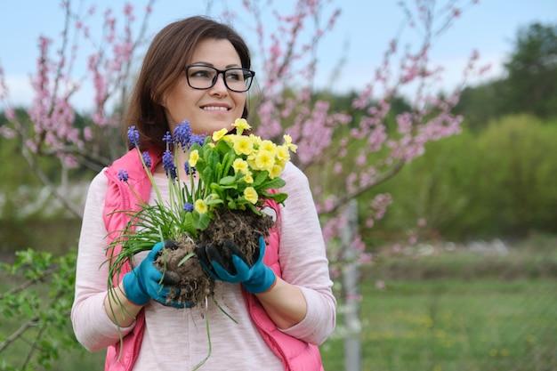 Mulher em luvas de jardim com flores para plantar