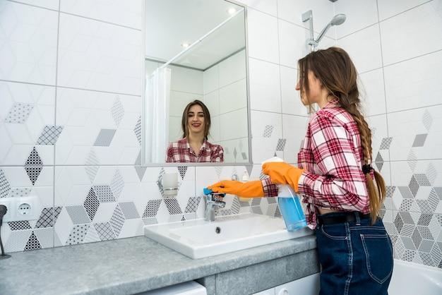 Mulher em luvas de proteção segurando um spray e um pano, fazendo tarefas no banheiro, limpando a torneira de água.