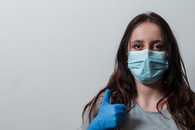 Mulher em luvas médicas e uma máscara protetora mostra como.