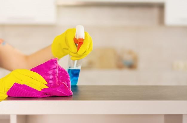 Mulher em luvas protetoras, limpando a poeira usando o pulverizador e espanador de limpeza. conceito de serviço de limpeza.