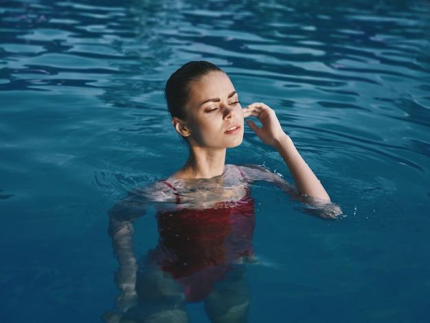 Mulher em maiô na piscina ao ar livre olhos fechados luxo lazer
