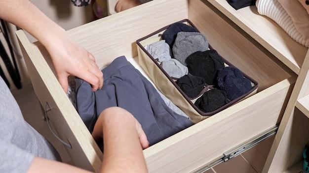 Mulher em mãos de camiseta cinza escolhe meias enroladas na gaveta aberta de um grande armário de madeira no closet contemporâneo em casa, vista de perto