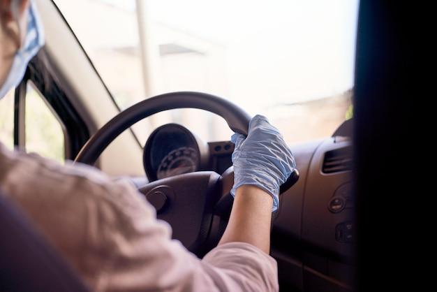 Mulher em máscara cirúrgica e luvas dirigindo carro