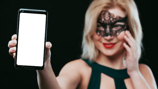 Mulher, em, máscara preta, segurando, smartphone