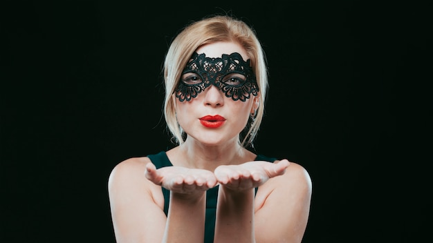 Mulher, em, máscara preta, soprando beijo