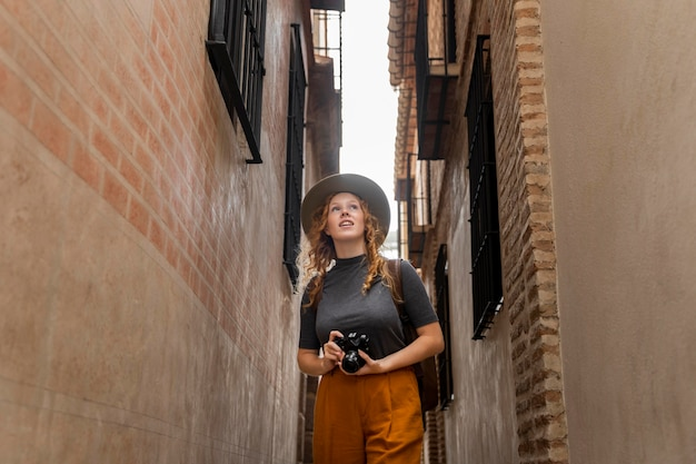 Mulher em meados de tiro com chapéu e câmera