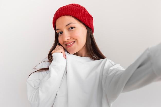 Mulher em meados de tiro com chapéu tirando selfie