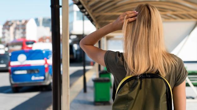 Mulher em meados de tiro com mochila na estação de ônibus