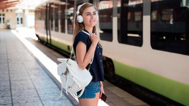 Mulher em meados de tiro com mochila na estação de trem