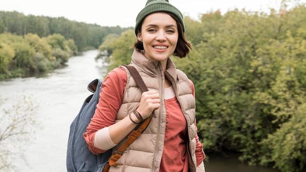 Mulher em meados de tiro posando em frente ao rio