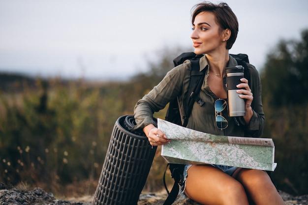 Mulher, em, montanha, com, viaje saco, olhar, mapa