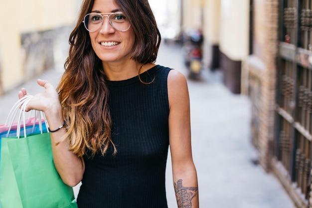 Mulher em óculos com bolsas de papel