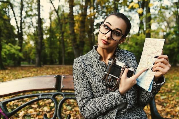 Mulher em óculos de grande porte com câmera e um mapa turístico