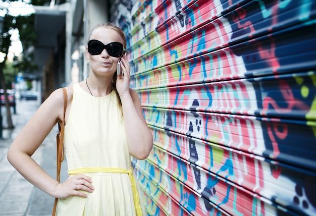 Mulher em óculos de sol conversando em um celular