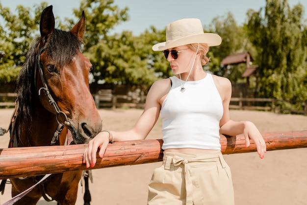 Mulher, em, óculos de sol, e, chapéu vaqueiro, perto, um, cavalo marrom