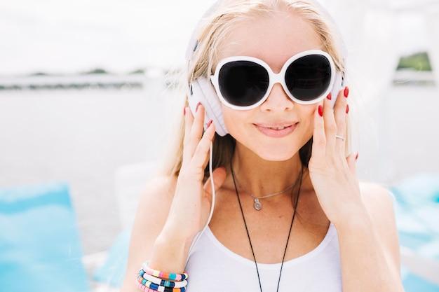 Mulher em óculos de sol e fones de ouvido