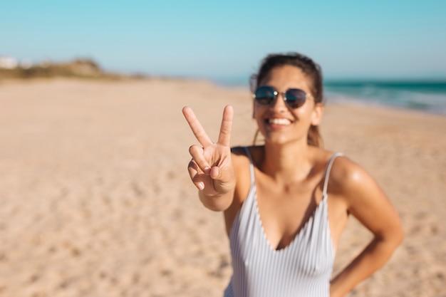 Mulher em óculos de sol fazendo v suspiro