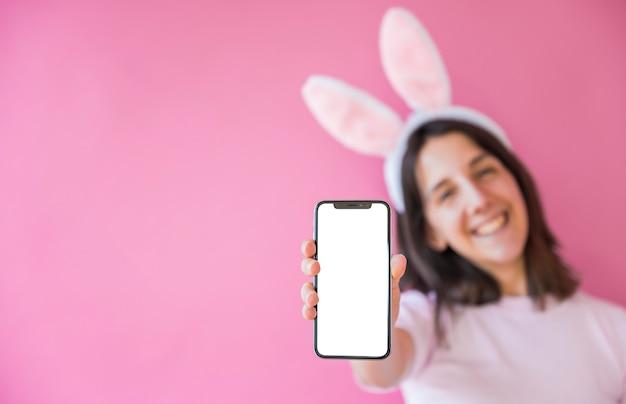 Mulher, em, orelhas bunny, segurando, smartphone, com, em branco, tela