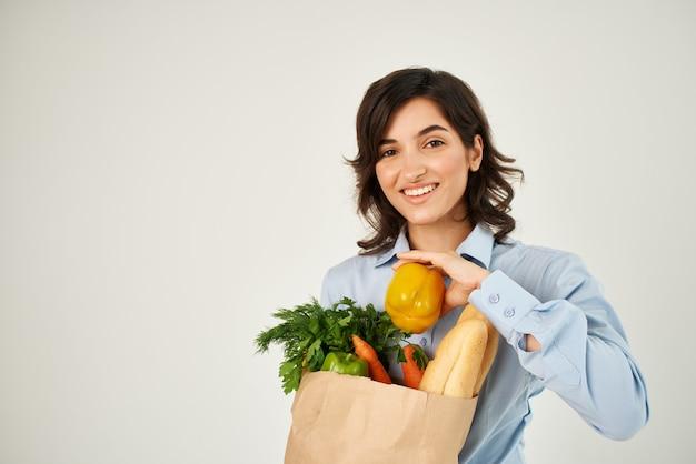 Mulher em pacote de camisa azul com fundo claro de alimentos saudáveis de mercearia