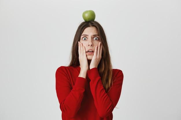 Mulher em pânico chocada com alvo de maçã verde na cabeça