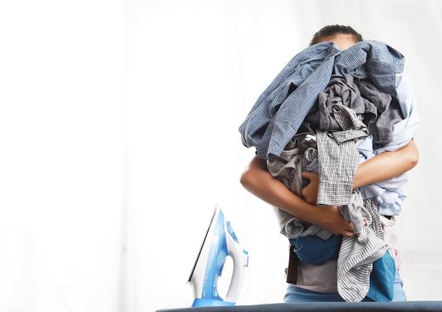 Mulher em pé abraçando roupas e ferro elétrico azul