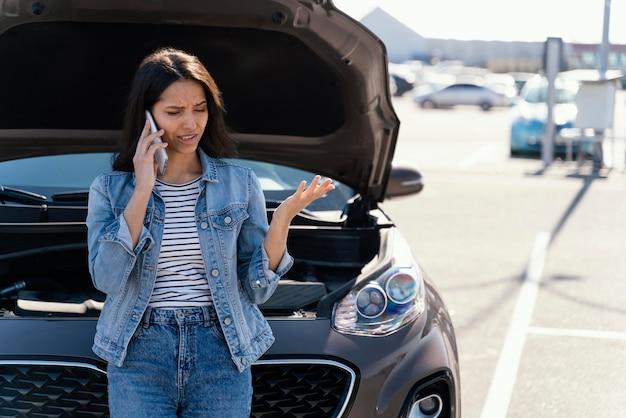 Mulher em pé ao lado de seu carro quebrado