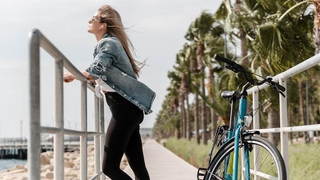 Mulher em pé ao lado de sua bicicleta