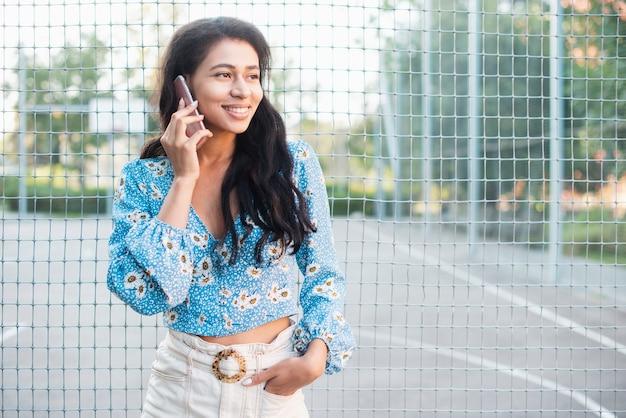 Mulher em pé ao lado de um campo de basquete, falando ao telefone