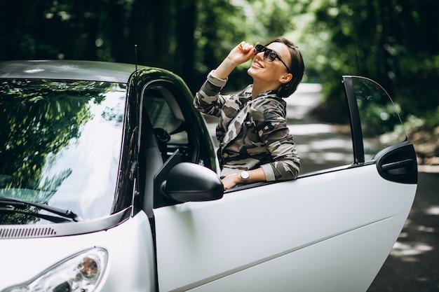 Mulher em pé ao lado do carro no parque
