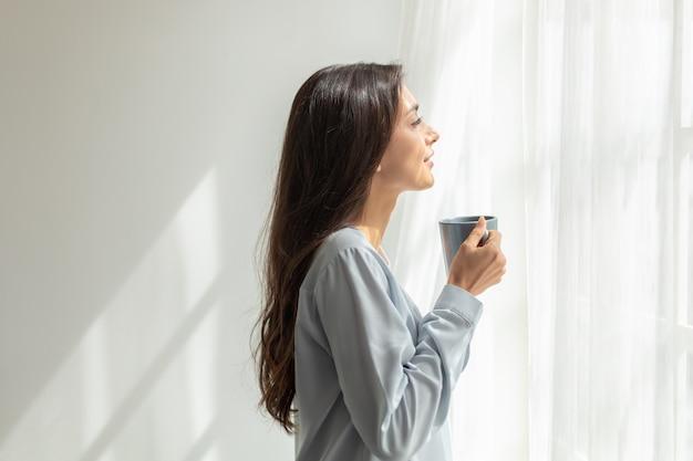 Mulher em pé beber café e abrindo as cortinas da janela respirar ar fresco exercício de alongamento no quarto