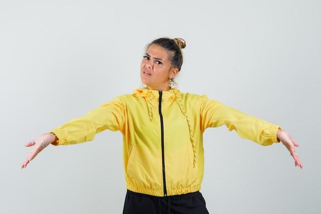 Mulher em pé com os braços bem abertos em um terno esporte e parecendo sombria, vista frontal.