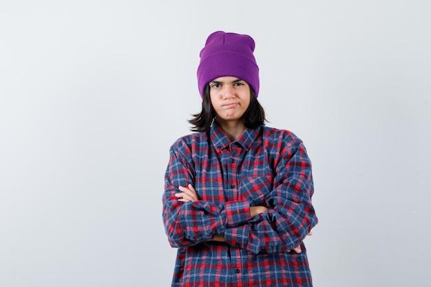 Mulher em pé com os braços cruzados e camisa xadrez