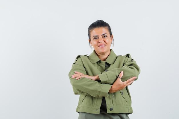 Mulher em pé com os braços cruzados no paletó, camiseta e aparência alegre