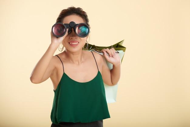 Mulher em pé com sacolas de compras e olhando através de binóculos