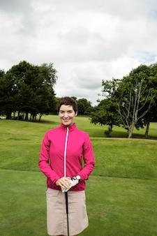 Mulher em pé com taco de golfe no campo de golfe