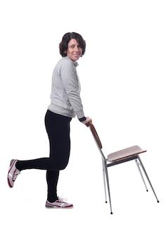 Mulher em pé com uma cadeira em fundo branco