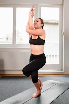 Mulher em pé com uma perna só no conceito de ioga em casa