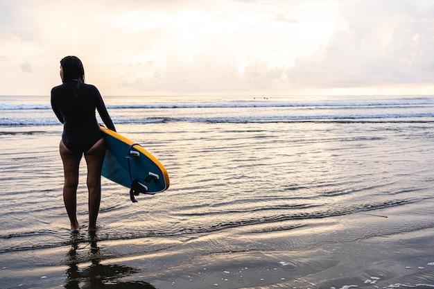 Mulher em pé com uma prancha de surf na praia