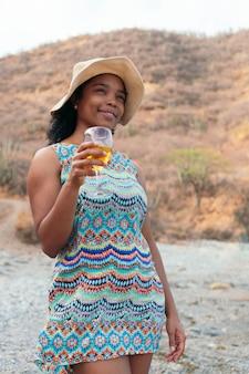 Mulher em pé com uma taça de vinho nas mãos
