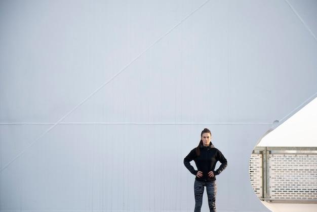 Mulher em pé contra a grande parede branca